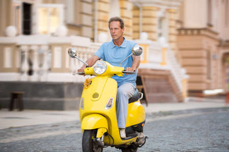 Adult man rides yellow scooter. Scooter on the empty road. Good fuel accelerates engine. Compact mean of transport. Banco de Imagens