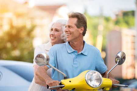 more mature: Man and woman on scooter. Mature couple is smiling. Trip is more fun together. Vacation and tourism. Stock Photo