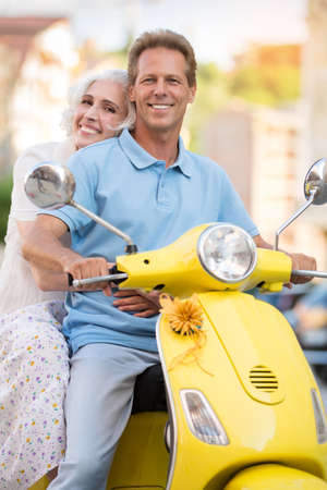 keen: Man and woman are smiling. Mature couple on yellow scooter. Keen on tourism. Keep active lifestyle.