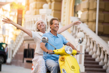 ours: Man and woman ride scooter. Adult lady with raised arms. Feel free and travel far. The world is ours. Stock Photo