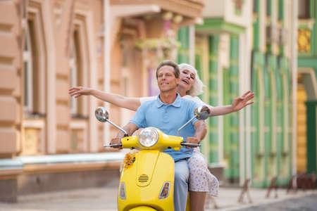El par se está montando un scooter. el hombre y la mujer sonriente. Valorar el tiempo que pasan juntos. Todos los caminos están abiertos.