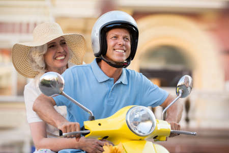 unstoppable: Mature couple on scooter smiles. Guy in a helmet. Hear the roar of motor. We are unstoppable.