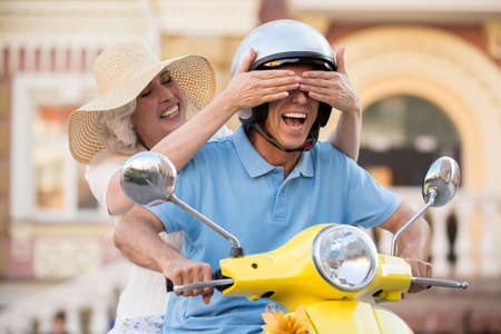 Woman closes mans eyes. Smiling mature couple on scooter. Jokes on the road. Guess where we are.