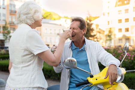 hilarious: Man with ice cream laughing. Couple of mature people. Hilarious moment of the trip. When theres nothing to do. Stock Photo