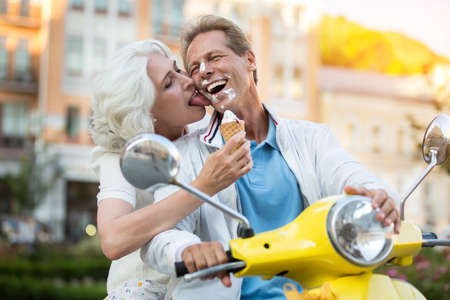 Face smeared in ice cream. Laughing man and woman. Feel no shyness. Great time for travels. Stock Photo