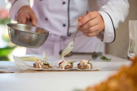 Handen met steelpan en lepel. Bruine stukjes vlees. Roquefort-saus voor medaillons. Proef het meesterwerk. Stockfoto