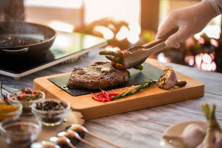 mastery: Tongs hold fried asparagus. Roasted garlic and meat. You should try ribeye steak. True mastery of chef. Stock Photo