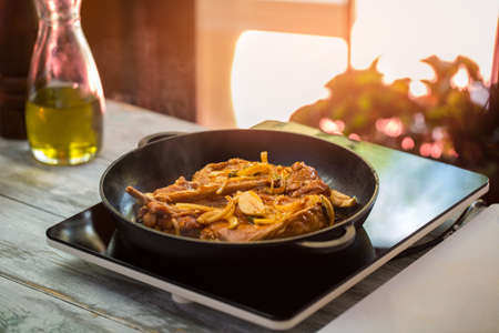 Black frying pan with meat. Pieces of garlic and onion. Recipe of spicy pork. How to prepare appetizing dinner. Stock Photo