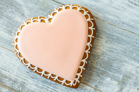 sugar cookie: Heart shaped cookie with glaze. Light pink frosted biscuit. Icing made of sugar. Express your love.
