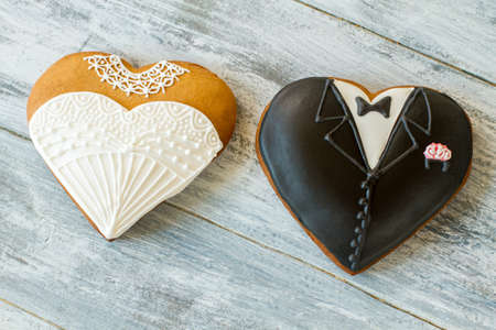 best regards: Wedding cookies on gray background. Biscuit shaped as tuxedo. Sweet treats for loving hearts. Best regards to newlyweds.