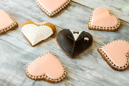 Wedding cookies on wooden background. Heart biscuits with glaze. Newlyweds and witnesses. Love is everywhere.
