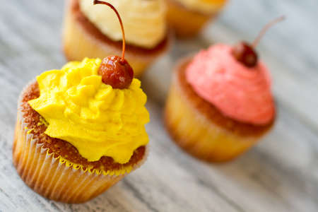 proven: Cupcake with yellow icing. Small baked dessert. Proven recipe of sweets. Buttercream and cherry. Stock Photo