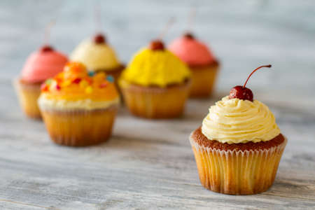Cupcake with beige frosting. Cherry on top of cream. Try the new flavor. Simple appetizing dessert. Stock Photo