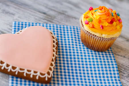 simplest: Orange cupcake and heart cookie. Confectionery on a napkin. Delicious surprise for loved ones. Beauty in the simplest things. Stock Photo