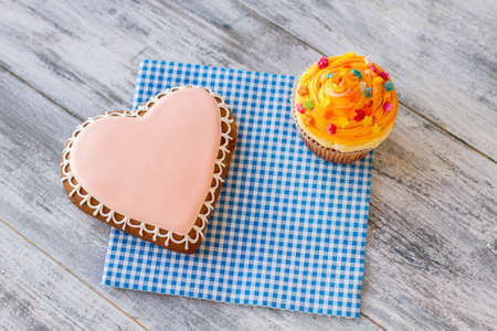 congratulate: Heart cookie and orange cupcake. Confectionery on napkin. Sweet treats and good feelings. Congratulate your loved ones.