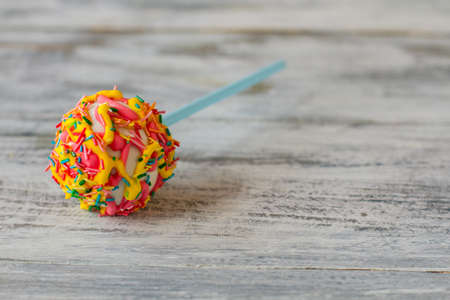Cake lollipop with sprinkles. Candy on wood background. Sweeten up the life. Youll never forget this taste.