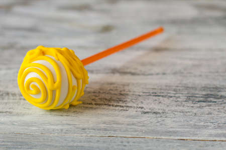 Cake pop with yellow icing. Candy lying on gray surface. Proven recipe of good mood. Sweeten up your day. Stock Photo