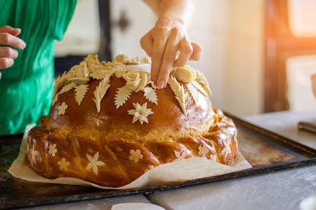 oven tray: Ladys hand touches decorated pastry. Bread on oven tray. Professional baker makes wedding bread. Dish for a ceremony. Stock Photo