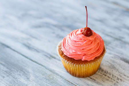 here's: Cupcake on wooden background. Pink cream and cherry. Heres a recipe of joy. Eat dessert with pleasure.