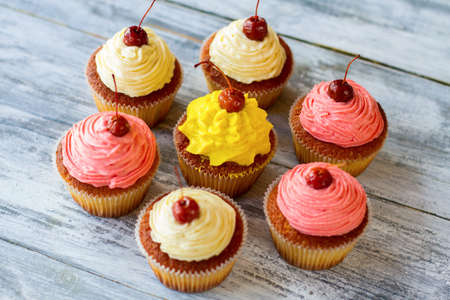 sweet treats: Cupcakes with icing. Desserts on gray background. Sweet treats made at home. Fresh ingredients and simple recipe.