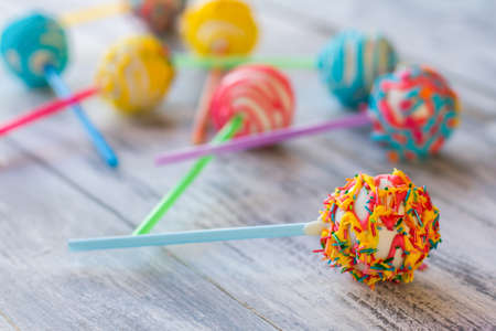 happier: Bright candy on a stick. Cake pop with icing. How to make children happier. White chocolate and cream filling.
