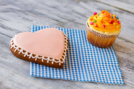 sense: Orange cupcake and heart biscuit. Confectionery on blue napkin. Love is sense of life. Wonders in simple things.