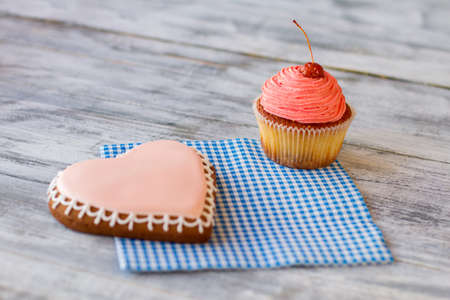 joys: Pink heart cookie and cupcake. Baked sweets on napkin. Crispy biscuit and soft cake. Share small joys of life.