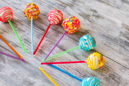 Glazed candies on sticks. Colorful sweets on wooden background. Easy recipe of cake pops. Kids will be happy.