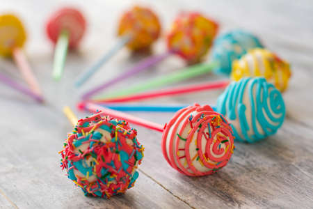 Sweets with frosting. Colorful candies on wooden surface. Cake pops for kids. Taste of a fun party. Stock Photo