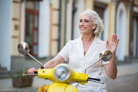 Woman on scooter waves hand. Mature lady kindly smiling. Greeting people on the way. Trip to new place.
