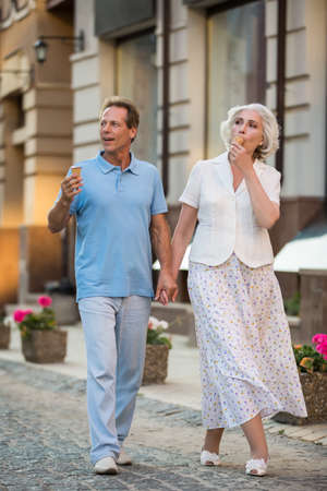 stroll: Couple holding hands. Mature woman eats ice cream. Best route for a stroll. Snack on the go.