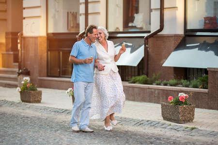 cherish: Coppia giovane a piedi e sorridente. L'uomo e la donna per mano. Allegro passeggiata durante il giorno. Amare ogni momento insieme.