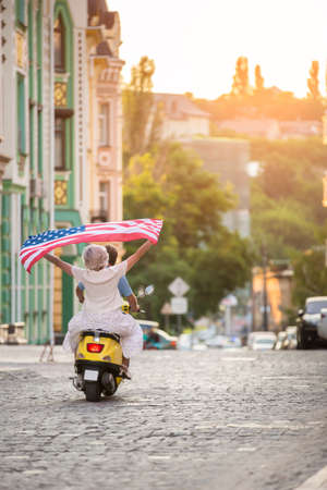 absolute: Couple on yellow scooter. Woman holds flag of USA. Ride into the sunset. This is absolute freedom.