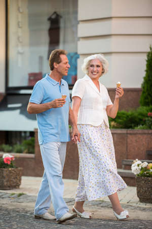 more mature: Mature couple is holding hands. People with ice cream walking. Vacation is more fun together. Walk through the home city.