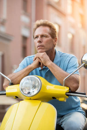 Adult man sits on scooter. Guy with thoughtful face. Need bright idea. I dont know this place. Stock Photo
