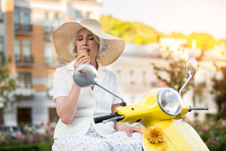 ice cream woman: Mature lady eating ice cream. Woman sits on a scooter. Relax and enjoy cool dessert. Trip went very well.