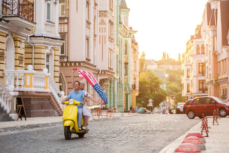 unforgettable: Mature couple riding on scooter. Woman holds flag of USA. Time to ride home. This vacation was unforgettable. Stock Photo