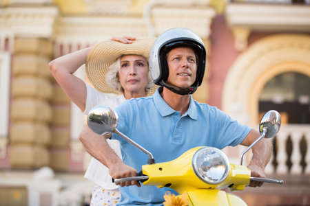 risky: Man with woman on scooter. Guy in a helmet. Must overcome long way. Risky tourists choose a path.