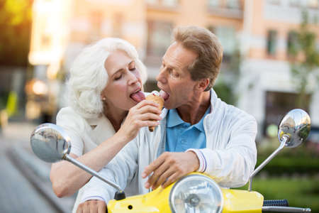 Mature couple sharing ice cream. People are sitting on scooter. Enjoy what you have today. Unforgettable summer tour. Stock Photo