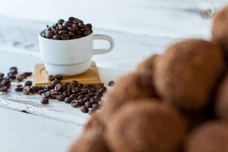 White cup with coffee beans. Dark grains on wooden surface. Caffeine boosts energy. Basic ingredient for delicious drink. Stock Photo