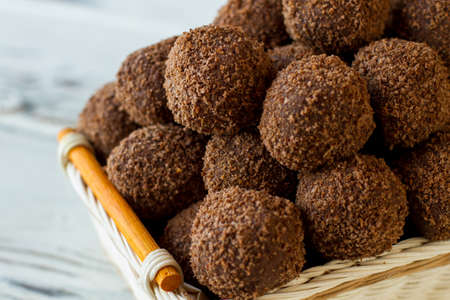 Basket with brown sweets. Little desserts covered in crumbs. Homemade chocolate rum balls. Cocoa powder and biscuits.