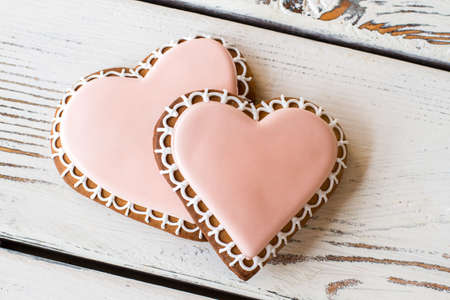 unforgettable: Pair of heart-shaped biscuits. Light pink icing on cookies. Unforgettable taste of love. Small delicious gift.