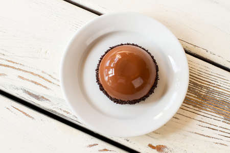 Small glazed cake on plate. Top view of brown dessert. Mirror glaze and chocolate mousse. Freshly made dish in cafeteria.