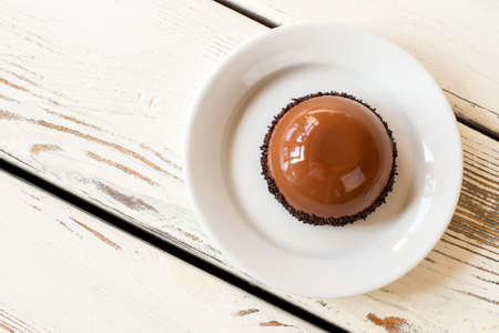 Top view of glazed cake. Brown dessert on white plate. Sweet dish with chocolate mousse. New delicacy in cafe.