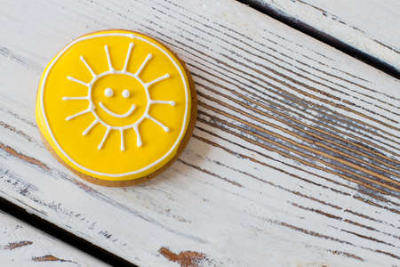 simplest: Cookie with smiling sun picture. Yellow frosted biscuit. Simplest recipe of joy. Sweet pastry made at home.