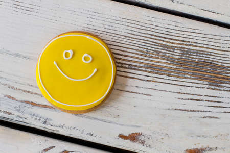 simplest: Smiley biscuit on wooden background. Round cookie with glaze. Simplest recipe of great mood. Dessert charges you with energy.