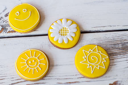 simplest: Top view of iced biscuits. Yellow cookies with decoration. Smiley face and sun. Art starts with simplest things.