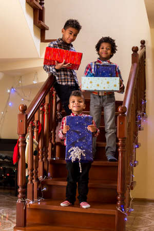 say cheese: Black children holding Christmas presents. Boys hold presents on staircase. Everyone say cheese. Moment to remember.