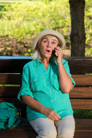 tariff: Surprised woman with a phone. Senior lady on the bench. Tariff with lowest prices. Cheap calls to any country. Stock Photo