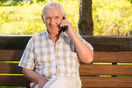 relatives: Smiling elderly man with phone. Senior male on a bench. I miss my relatives. Grandpa calls home.